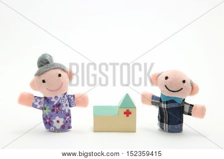 Puppet of the old couple and hospital on white background. Nursing care.