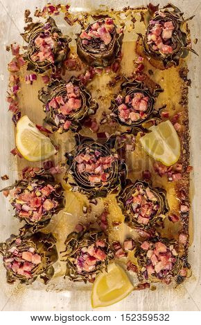 A photo of artichoke hearts cooked with jamon and red onions, a traditional Spanish meal, shot in a tray from above, with slices of lemon
