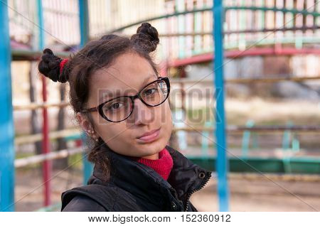 Portrait of a girl with glasses on the background of the playground