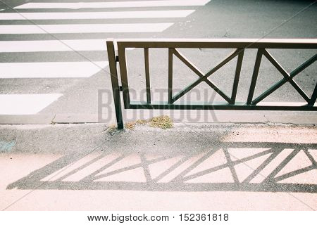 Metal fence near road and crossing zebra. Protective barrier, that separates driving part from sidewalk. Safety on street concept
