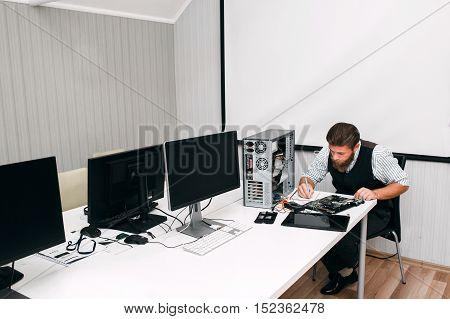 Programmer testing work equipment in open space. System administrator conduct an inventory of computers and screens in office and note results in notebook