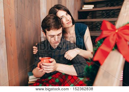 Smiling brunette hugging her boyfriend, close-up. Happy couple having rest on wooden stairs in their home, copy space. Happy family, love, care, holiday concept