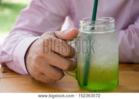 Man holding a mug of juice on wooden table