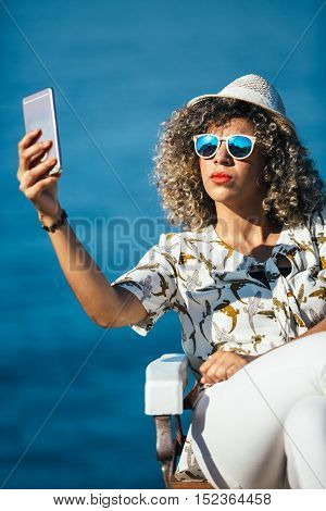 Portrait of beautiful mixed race woman wearing sunglasses and hat makes selfie with smartphone