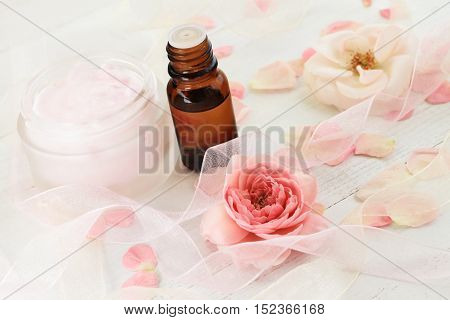 Rose scent beauty care cosmetic products. Bottle of essential oil, facial moisturizer, pink pastel colored fresh flowers, feminine lace decor.