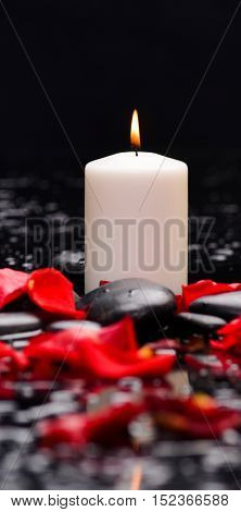Red rose petals with andle and therapy stones