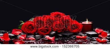 Lying down branch red rose with candle and therapy stones