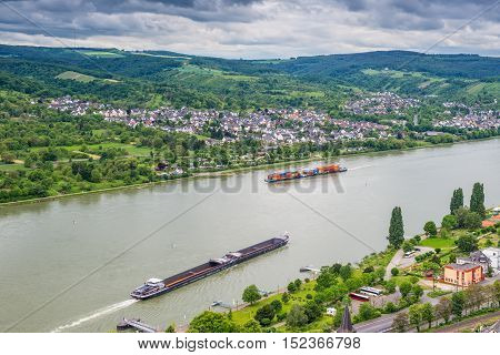 Brey Germany - May 23 2016: Сontainer and cargo ship on the Rhine River Rhine Valley UNESCO World Heritage Site Germany. Brey and Rhens in background. The Rhine river in Europe plays a major role in freight transport for the 21st century connecting many t