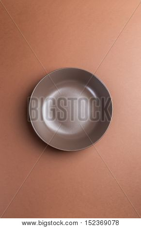 Brown plate on brown background above view.Useful as a food background.