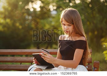 Cute girl holding a tablet pc and credit card. Payment for online purchases. Banking online.