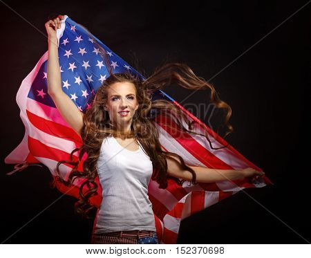Young attractive girl holding a waving US flag. She a T-shirt and shorts with a print of the flag. Long curly hair. Patriot country.