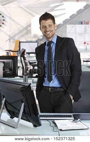 Portrait of satisfied young caucasian business associate standing at office with hands in pocket, smiling, suit and tie.