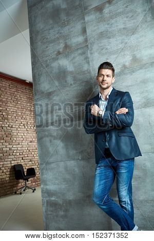 Confident businessman in casual business wear standing at concrete wall, looking away.