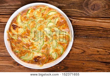Pie with zucchini on the wooden table top view. Healthy eating.