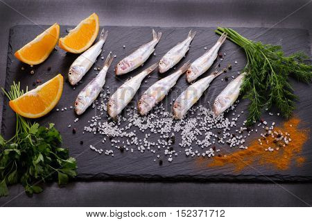 Fresh fish on a dark background with spices