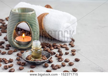 Aroma lamp with coffee essential oil on woven mat spa background horizontal copy space