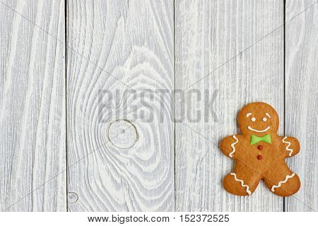 Christmas homemade gingerbread man cookie on wooden background