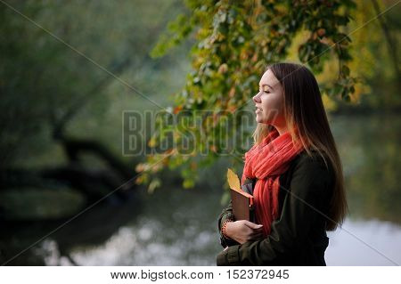 Autumn. Lovely girl in a bright red scarf walks in autumn park. Trees reflected in the pond. Through foliage the sunlight makes the way. In the hands of a girl is notebooks backpack on her shoulder.