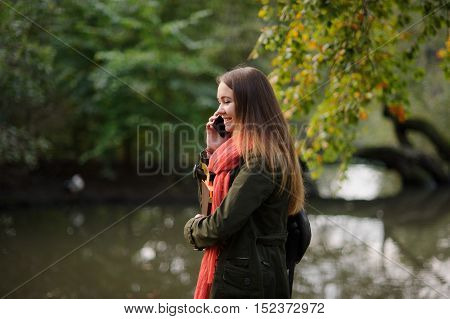 The young attractive woman walks in the autumn park. She speaks by the mobile phone and smiles. Autumn trees are reflected in a pond. Wonderful early autumn.
