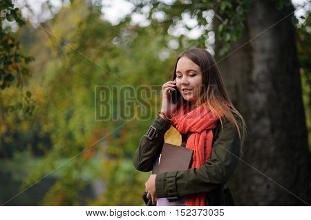 Autumn. Lovely girl in a bright red scarf is leaning against the trunk of a large tree. She is talking on a cell phone and smiling. In the hands of a girl holding notebooks and yellow leaf.