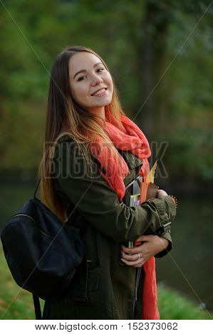 Cheerful student on the background of autumn park. Cute girl in coat and bright red scarf looks into the camera and smiles. She is holding textbooks with a yellow autumn leaf.