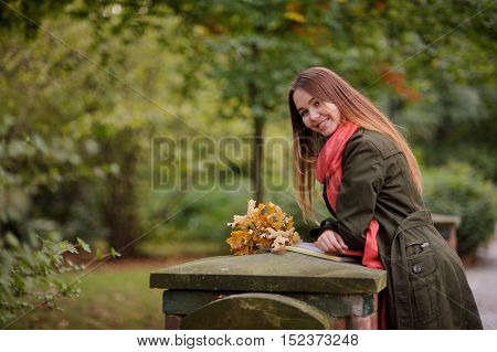Cheerful girl on background of autumn park. Cute student in bright red scarf looks into the camera and smiling. She is leaning on stone pedestal. Before her lie notebooks and bouquet of autumn leaves.