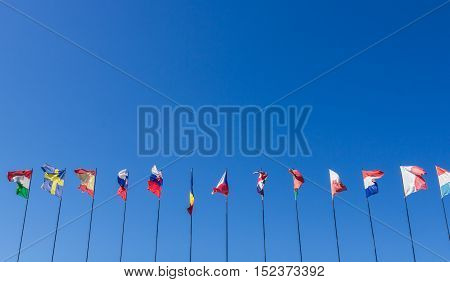 Row of national flags against blue sky