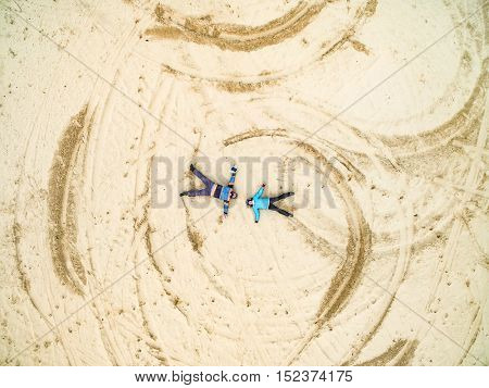 Aerial view - man and girl lie on a sandy ground, top view