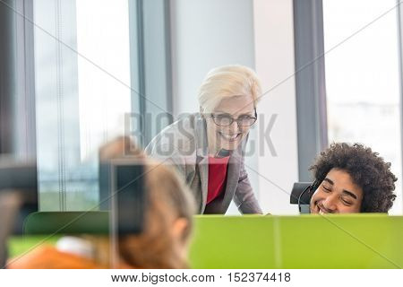Smiling female manager assisting operator wearing headset in office