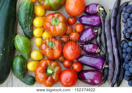 Autumn food background. Beans grapes tomatoes peppers zucchini cucumber on light wooden surface. Top view.