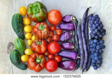 Autumn food background. Beans grapes tomatoes peppers cucumber on light wooden surface. Top view.