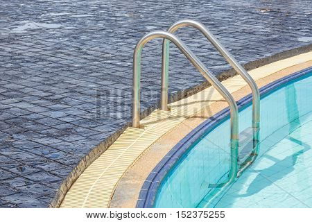 The metallic ladder for using entrance to swimming pool.