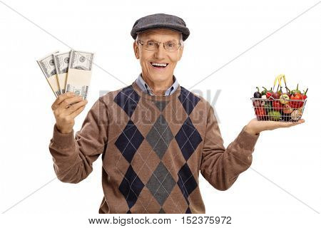 Cheerful senior holding a small shopping basket full of fruits and vegetables and money bundles isolated on white background