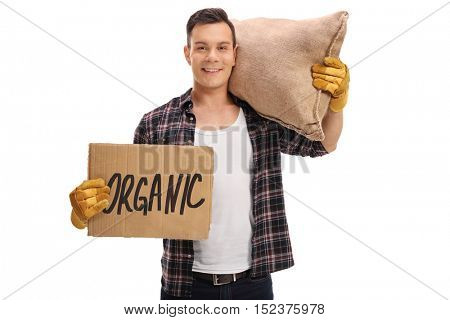 Male agricultural worker holding a cardboard sign that says organic and a burlap sack isolated on white background