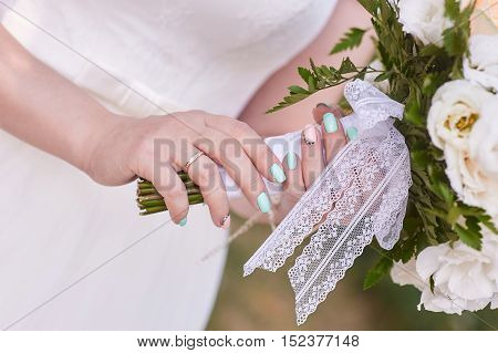 Bride hand with ring holding a bridal bouquet of white roses close up