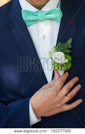 groom boutonniere adjusts his hand in a jacket pocket close up