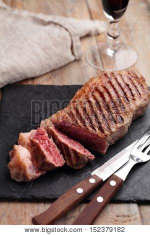Grilled marbled beef steak on a slate cutting board