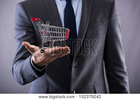 Buisinessman holding shopping cart in online shopping concept