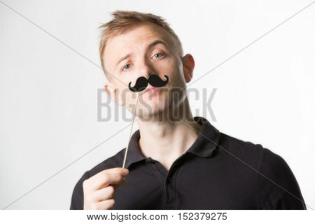 Portrait of an attractive young man wearing a retro style fake mustache.