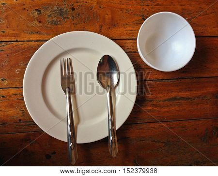 Empty white plastic dish with spoon and fork on old wooden background