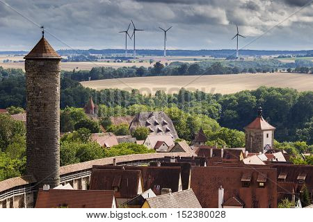 A quaint little medieval town in Germany surrounded by wind turbines and farmland.