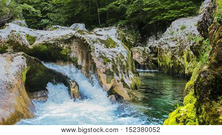 A small blue waterfall in Slovenia near lake Bled placed in a wild forrest.