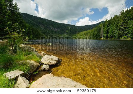 Lake with rocks in the middle of Sumava forests