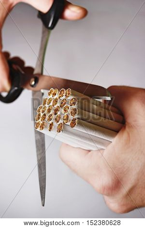 Closeup of hands cutting bundle of cigarettes against gray background