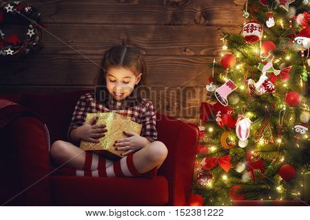 Merry Christmas and Happy Holiday! Cute little child girl with magic gift box on Christmas.