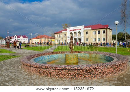 SENNO BELARUS - OCTOBER 8 2016: Unidentified people walk on town square near District House of Culture and fountain during regional festival-fair