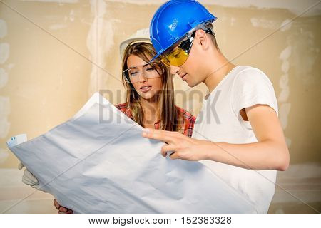 Young couple discussing design project of their new apartment. Repair, construction and mortgage concept.