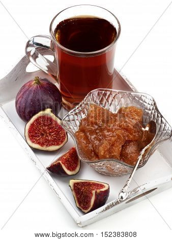 Arrangement of Delicious Homemade Fig Jam in Glass Kremanka with Fresh Fig Fruits and Glass Cup of Tea in White Wooden Tray closeup on White background