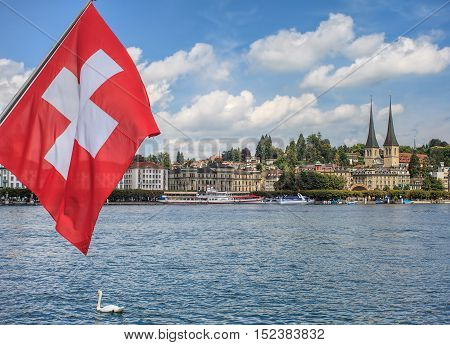 View in Lucerne, Switzerland: flag of Switzerland, Lake Lucerne with the city of Lucerne in the background.