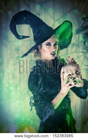 Frightening witch girl in medieval dress and a hat holding a skull in a mysterious abandoned house. Witchcraft, witch.   Halloween concept.